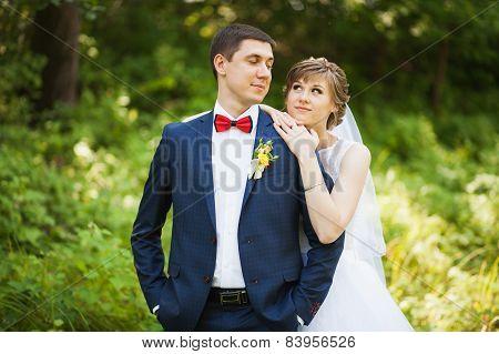 happy bride, groom standing in green park