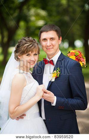 happy bride, groom standing in autumn park