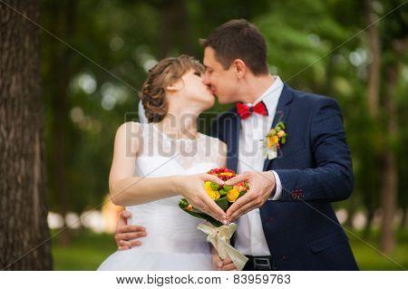Happy bride, groom standing in green park, hands show heart - symbol of love