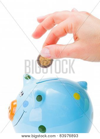 Hand Putting A Coin Into Piggy-bank