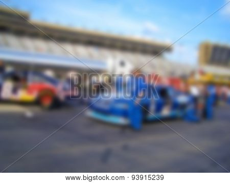 Blurred Background Image of Race Cars on Pit Row poster