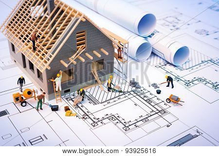 building house on blueprints with worker - construction project
