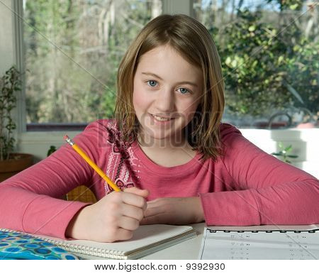 girl happily doing her homework