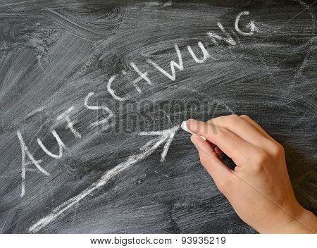 Hand writing with chalk on a blackboard the German word upswing