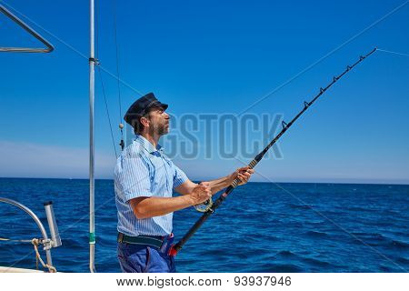 Beard sailor man fishing rod trolling in saltwater in a boat trolling with captain cap