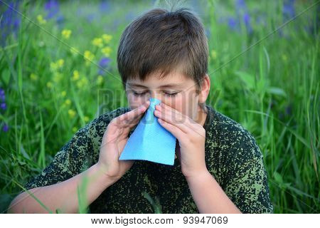 Teen Boy With Allergies In Flowering Herbs