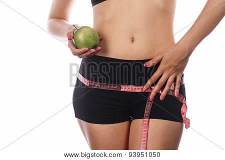 Young slim athletic woman measures buttocks and holding an apple. Isolated on white background. Concept of healthy food. poster