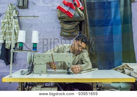 JODHPUR, INDIA - 10 FEBRUARY 2015: Tailor at work in textile factory after working hours.