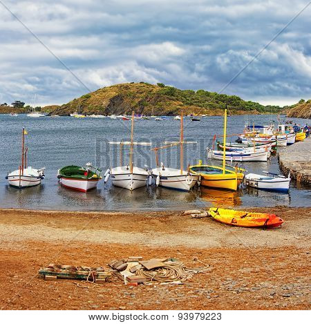 Boats on the beach and pier at stormy weather in Cadaques harbor poster