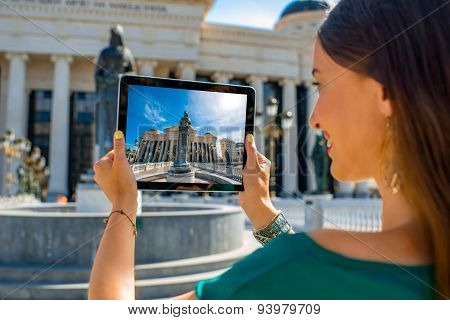 Woman photographing with digital tablet Maria Teresa monument in Skopje poster
