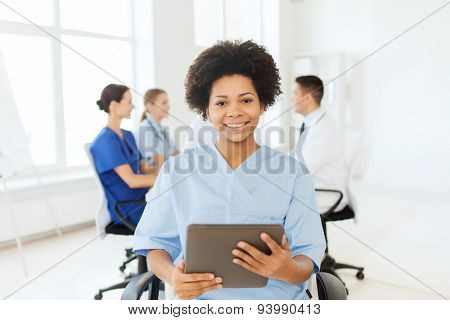 clinic, profession, people and medicine concept - happy african american female doctor or nurse with tablet pc computer over group of medics meeting at hospital poster