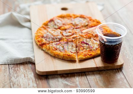 fast food, italian kitchen and eating concept - close up of pizza with cup of cola drink on wooden table