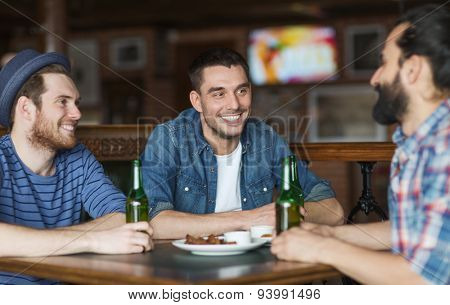 people, leisure, friendship and bachelor party concept - happy male friends drinking bottled beer and talking at bar or pub