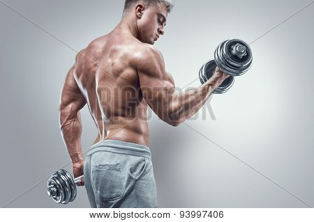 Power Athletic Man In Training Pumping Up Muscles With Dumbbells
