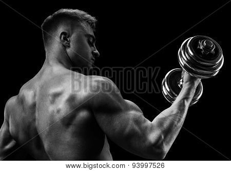 Closeup of a handsome power athletic man bodybuilder doing exercises with dumbbell. Fitness muscular body on dark background. poster