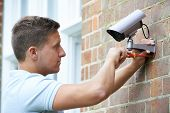 Security Consultant Fitting Security Camera To House Wall poster