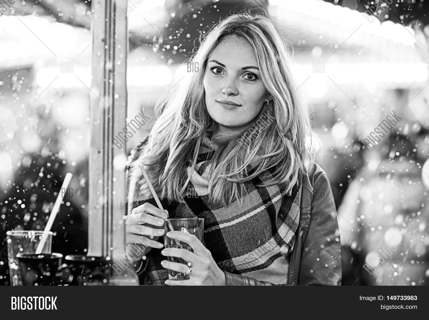 3a72cd3a4ebe Beautiful young woman drinking hot punch, mulled wine on German Christmas  market. Happy girl