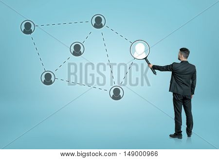 Back view of a businessman enlarging one of the social network icons connected by dotted lines with a magnifier. Searching and investigation. Employment issues. Global communication.