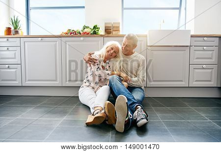 Happy beautiful woman being held by her loving husband while sitting on kitchen floor