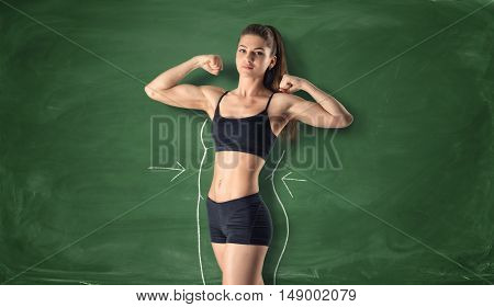 Cropped portrait of fitness girl showing her biceps with drawn fat around her body on the background of a chalkboard. Workout and sport. Self-improvement. Healthy lifestyle.