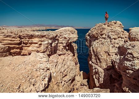 Young lady standing on the top of the cliff in the National Park of Ras Muhammad, Egypt