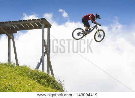 Freeride mountainbiker jumping from a wood platform