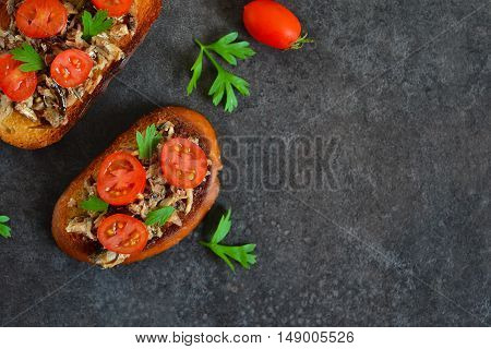 Toasts with sprats tomato and garlic on a black background with space for text background food