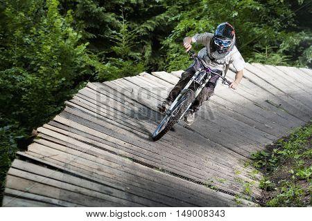 Extreme mountainbiker rides on wooden platform in bikepark