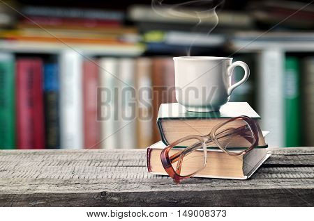 Hot coffee or tea cocoa chocolate cup on book and eyeglasses with copy space for text against the background of a bookshelf. Pile of books glasses and cup on a table in the library