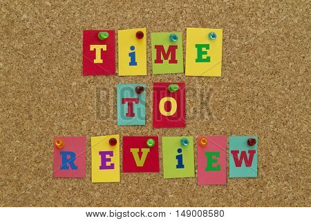 TIME TO REVIEW message written on colorful sticky notes pinned on cork board.