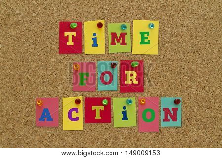 TIME FOR ACTION message written on colorful sticky notes pinned on cork board.