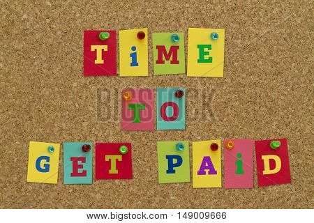 TIME TO GET PAID message written on colorful sticky notes pinned on cork board.