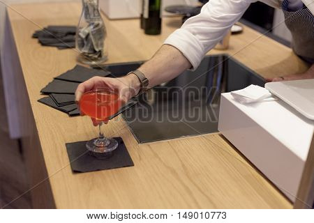 A bartender places a red alcoholic drink on a black beverage napkin.