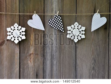 Snowflakes and handmade hearts on old wooden background. Attributes of the winter holidays. Family values. Memories. Nostalgia. Christmas in the village.