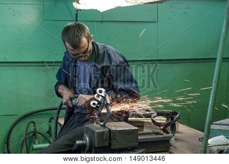 Tyumen, Russia - November 14, 2007: JSC Tyumenskie Motorostroiteli. Plant on production and repair of aviation engines. Worker grinds detail