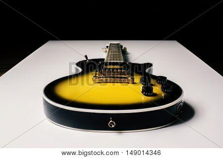 Electric sunburst guitar placed on white surface. Dark background