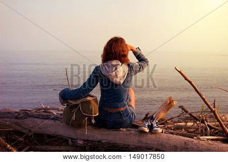 Hipster young tourist girl in jeans sneakers with a bag sitting back and enjoying sundown on a sea. Tourism ocean vacation tripping and active rest concept