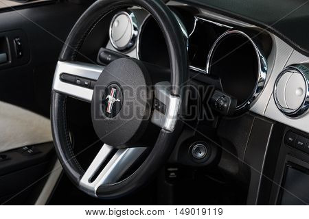 Moscow, Russia - September 10, 2016: Ford Mustang retro car wheel and dashboard