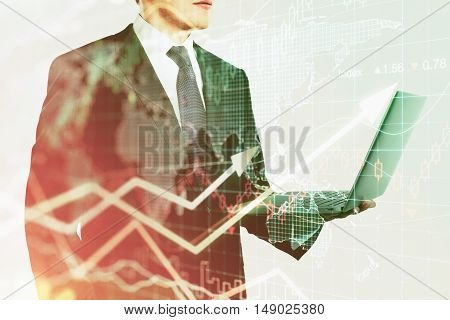 Businessman using laptop on abstract background with forex graph. Financial growth concept. Double exposure