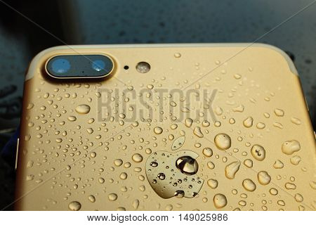 PARIS FRANCE - SEP 26 2016: New Apple iPhone 7 Plus unboxing and testing - pure gold iphone covered with rain water. New iPhone7 is one of the best waterproof smart phone in the world