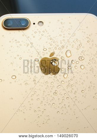 PARIS FRANCE - SEP 26 2016: New Apple iPhone 7 Plus unboxing and testing - rose gold model with double camera and water drops. New iPhone7 is one of the best waterproof smart phone in the world