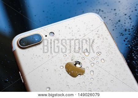 PARIS FRANCE - SEP 26 2016: New Apple iPhone 7 Plus unboxing and testing - rain drops on back of the phone. New iPhone7 is one of the best waterproof smart phone in the world