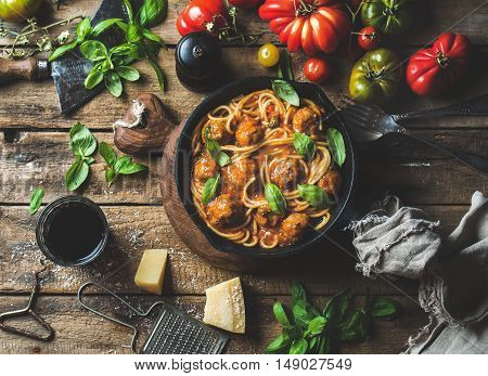 Italian pasta spaghetti with tomato sauce and meatballs in cast iron pan with Parmesan cheese, fresh basil, tomatoes and glass of wine over old rustic wooden background. Top view, horizontal composition