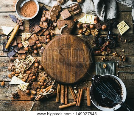Pieces of white, dark and milk chocolate, nuts, cocoa powder, melted chocolate and spices with wooden board in center. Hot chocolate cooking ingredients. Rustic background, top view, copy space