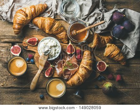 Breakfast with freshly baked croissants, ricotta cheese, figs, fresh berries, prosciutto, honey in glass jar and coffee espresso over rustic wooden background, top view, horizontal composition