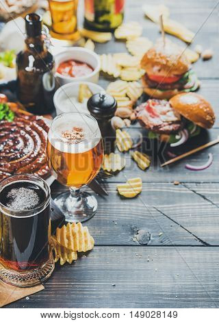 Beer and snack set. Oktoberfest food frame concept. Variety of beers, grilled sausages, burgers, potato chips and sauces on dark wooden scorched background. Selective focus, copy space