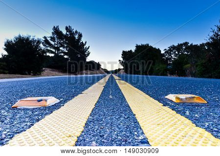 Double yellow line with yellow reflective pavement markers from a low vantage point