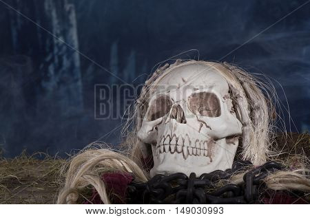 Grim reaper skull in a smoky halloween background