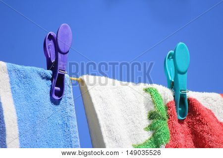 Bright colored towels pegged to a washing line against a clear blue sky