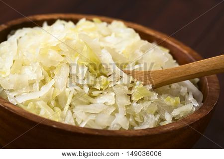 Sauerkraut in wooden bowl photographed with natural light (Selective Focus Focus one third into the sauerkraut)